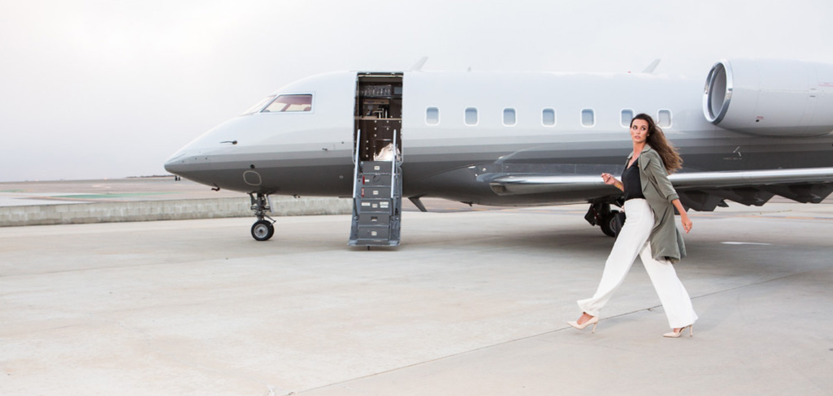 Elegant woman walking towards a private jet