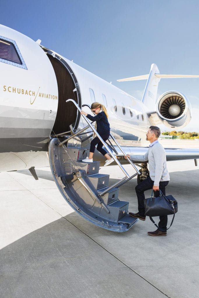 A woman and man getting on a private jet