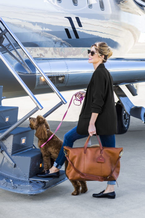 Woman boarding Schubach private jet with dog