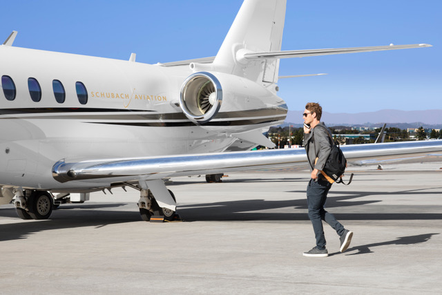 Young man on cell phone approaching private jet