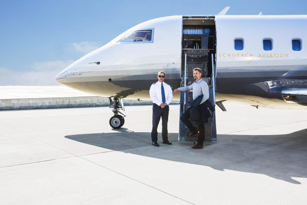 Pilot and passenger in front of private jet
